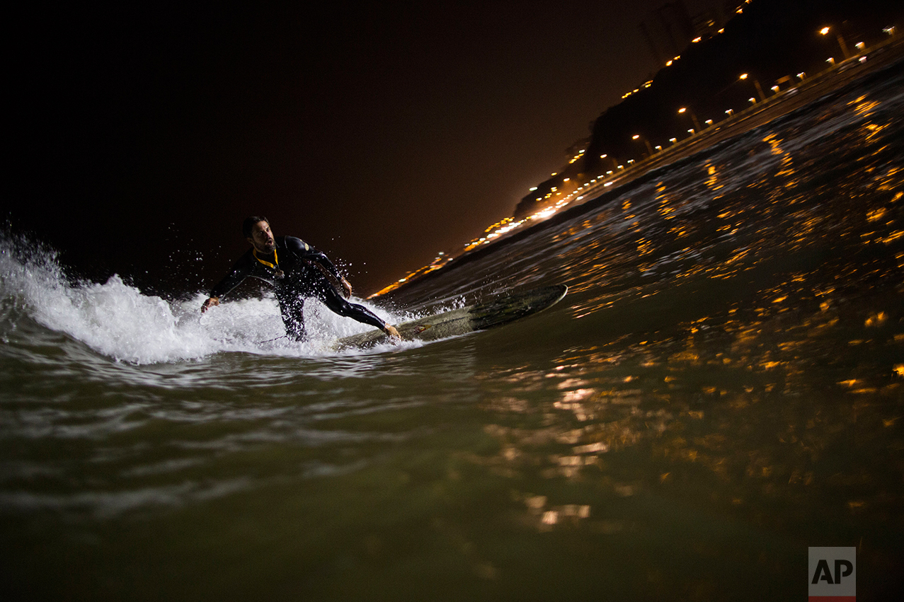 In this April 26, 2017 photo, Ernesto Benavides rides a wave in the waters of La Pampilla beach in Lima, Peru. As most Lima residents prepare to sleep, a handful of hardcore surfers descend on the only beach in Peru where they can ride the waves at night. (AP Photo/Rodrigo Abd)