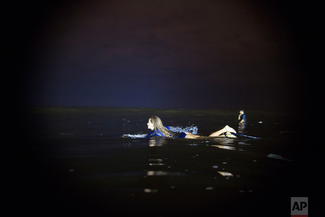 In this March 15, 2017 photo, Marie Schoene looks for a wave to surf in La Pampilla beach in Lima, Peru. Pampilla does not attract sharks, unlike some beaches in the United States and Australia. The greatest danger faced by night surfers is that they can crash into each other, blinded by the powerful floodlights. (AP Photo/Rodrigo Abd)