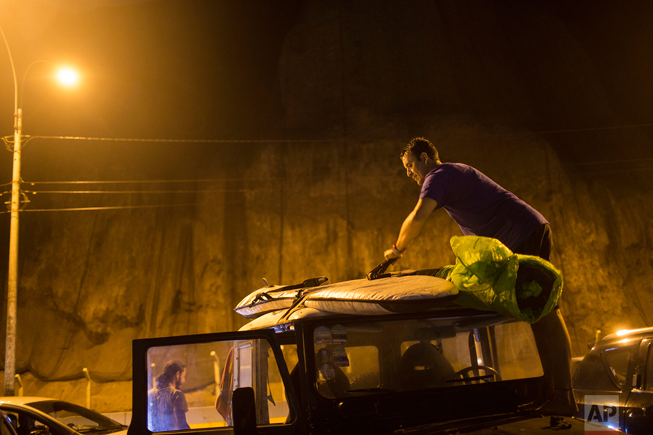 In this March 1, 2017 photo, surfer Mario Razzeto accommodates his board on the roof of a car after surfing in the waters of La Pampilla beach in Lima, Peru. Pampilla is the second beach in Latin America set up for night surfing. The Brazilian beach of Arpoador, one of the biggest surf landmarks in Rio de Janeiro, has had artificial lights since 1989. (AP Photo/Rodrigo Abd)