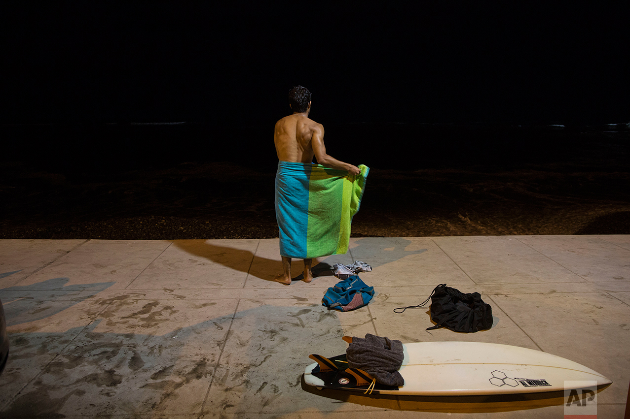 In this March 3, 2017 photo, a man wraps a towel around his waist after a night of surfing at La Pampilla beach in Lima, Peru. As most Lima residents prepare to sleep, a handful of hardcore surfers descend on the only beach in Peru where they can ride the waves at night. (AP Photo/Rodrigo Abd)