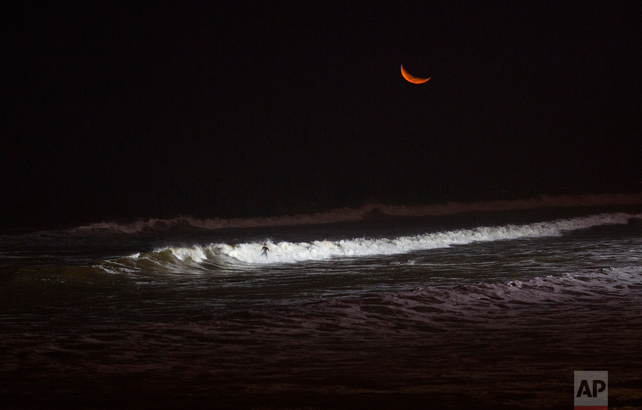In this March 2, 2017 photo, a man rides a wave in the Pacific Ocean waters of La Papilla beach in Lima, Peru. As most Lima residents prepare to sleep, a handful of hardcore surfers descend on the only beach in Peru where they can ride the waves at night. (AP Photo/Rodrigo Abd)