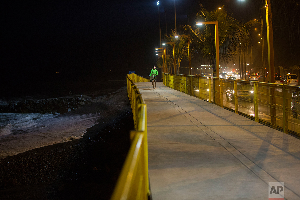 In this March 1, 2017 photo, a surfer walks along the promenade that lines La Pampilla beach in Lima, Peru. The Andean country has decked out Pampilla withfour 1,000-watt light like those used in soccer stadiums, providing enough illumination to surf after nightfall. (AP Photo/Rodrigo Abd)