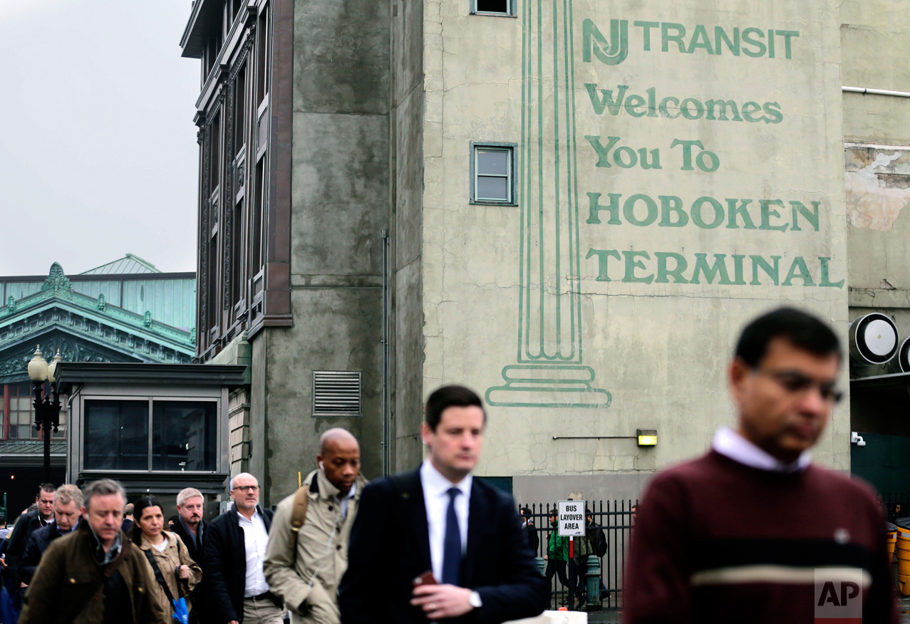 Commuters make their way to buses bound for New York City in Hoboken, N.J., Tuesday, April 4, 2017. A minor derailment on Monday at Penn Station involving a New Jersey Transit train and other rail issues are causing major problems for New York City metro area commuters. (AP Photo/Seth Wenig)