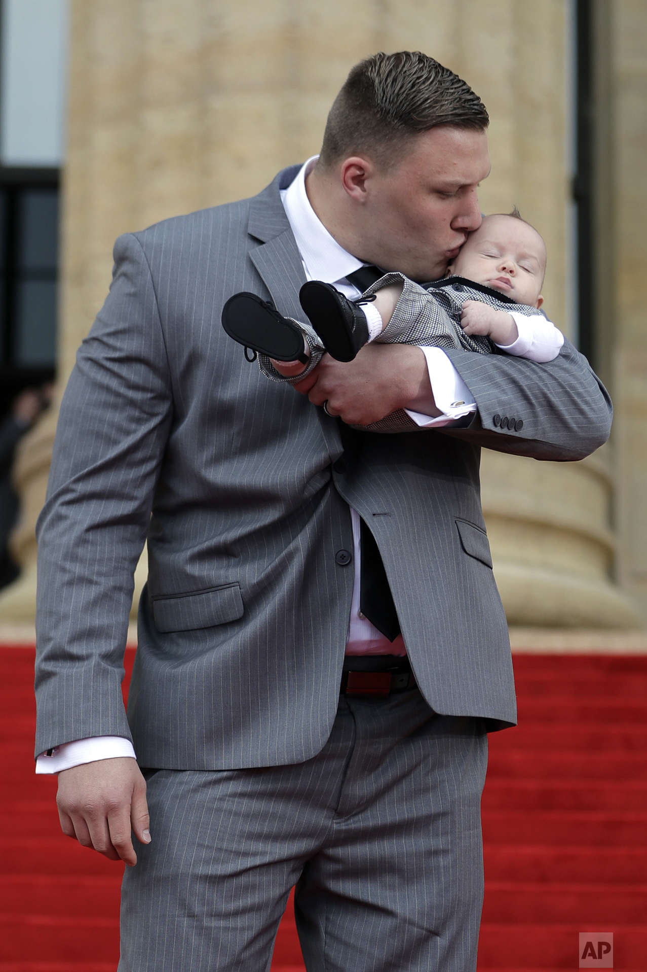 Utah's Garett Bolles arrives with his son Kingston for the first round of the 2017 NFL football draft, Thursday, April 27, 2017, in Philadelphia. (AP Photo/Julio Cortez)