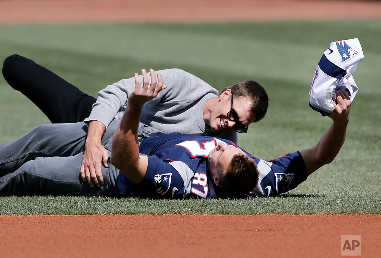 New England Patriots quarterback Tom Brady, top, tackles teammate Rob Gronkowski after he ran with Brady's recovered Super Bowl jersey as they joke around during Boston Red Sox Home Opening Day ceremonies at Fenway Park, Monday, April 3, 2017, in Boston. The Red Sox face the Pittsburgh Pirates in the baseball game. (AP Photo/Elise Amendola)
