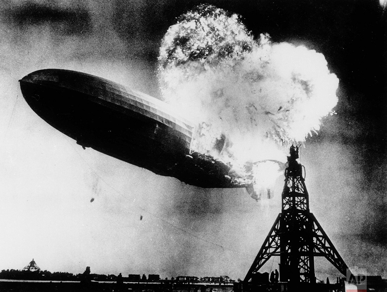 """This May 6, 1937 photo, provided by the Philadelphia Public Ledger, was taken at almost the split second that the Hindenburg exploded over the Lakehurst Naval Air Station in Lakehurst, N.J. Only one person is left of the 62 passengers and crew who survived when the Hindenburg burst into flames 80 years ago Saturday, May 6, 2017. Werner Doehner was 8 years old when he boarded the zeppelin with his parents and older siblings after their vacation to Germany in 1937. The 88-year-old now living in Parachute, Colo., tells The Associated Press that the airship pitched as it tried to land in New Jersey and that """"suddenly the air was on fire."""" (AP Photo)"""
