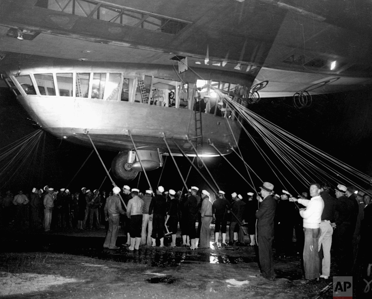 Spectators and ground crew surround the gondola of the German zeppelin Hindenburg as the lighter-than-air ship prepared to depart the U.S. Naval Station at Lakehurst, NJ, May 11, 1935, on its return trip to Germany. (AP Photo)