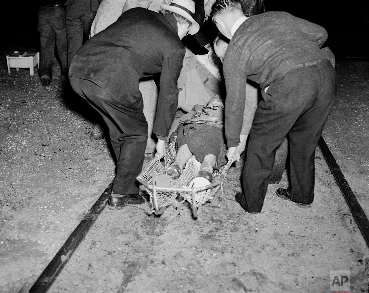 A victim of the Hindenburg disaster is taken away in a stretcher in the aftermath of the airship crash in Lakehurst, N.J., May 6, 1937.  The German-built zeppelin burst into flame in mid-air as it was landing after its transatlantic voyage, carrying 97 passengers and crew. Thirty-five people on board and one ground crew member were killed.  (AP Photo/Murray Becker)