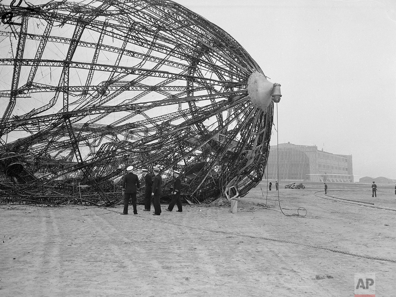 Members of the U.S. Navy Board of Inquiry inspect the wreckage of the German zeppelin Hindenburg on the field of the Lakehurst Naval Air Station in New Jersey, May 8, 1937.  The Hindenburg exploded after morning on May 6, killing 36 people.  (AP Photo)