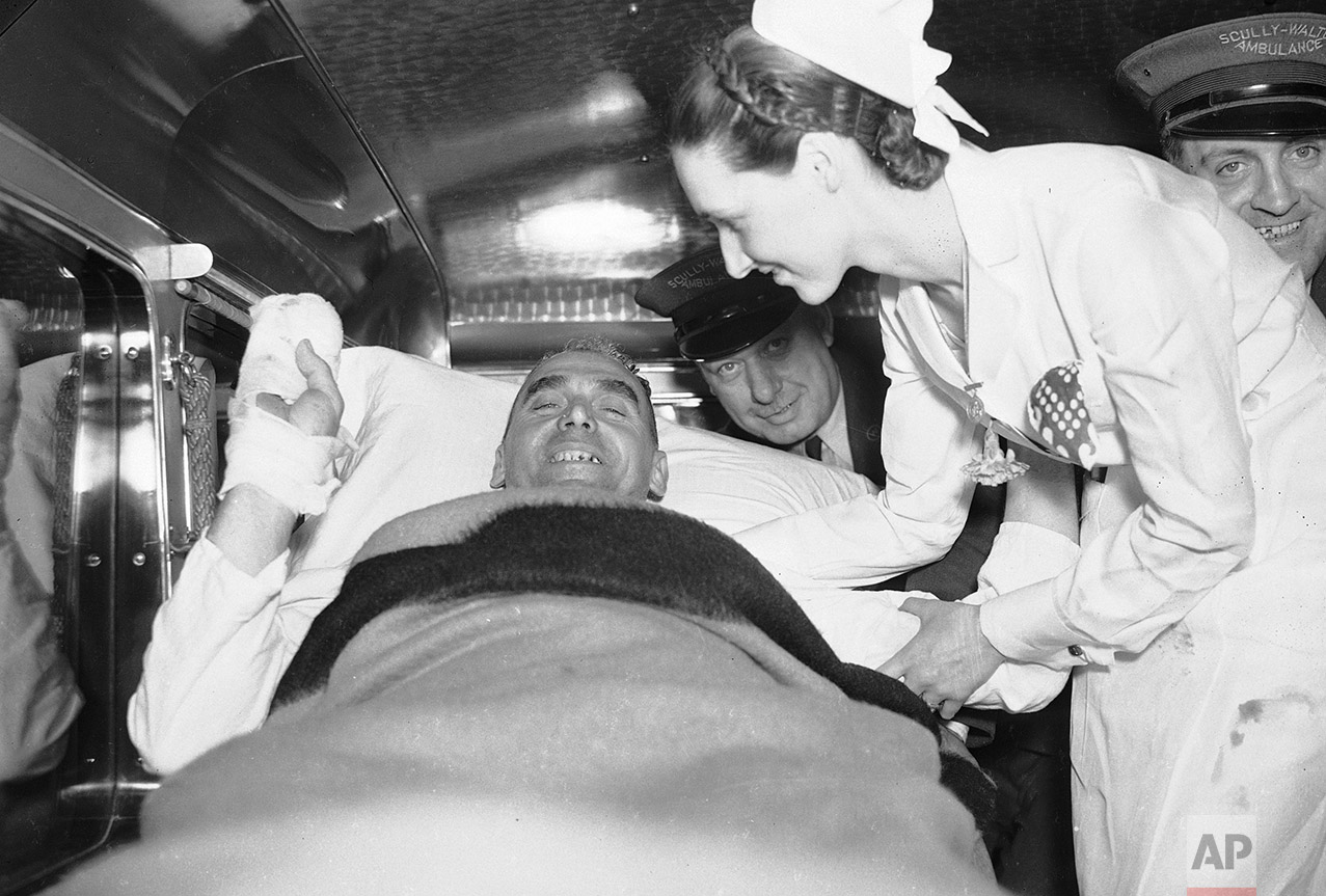 An unidentified survivor of the airship Hindenburg disaster, along with a nurse and unidentified emergency service workers are seen in an ambulance as the patient is transferred from Paul Kimball Hospital in Lakewood, N.J. to another area hospital, May 7, 1937. The German zeppelin exploded yesterday after mooring in Lakehurst Naval Air Station, killing 36 people.  (AP Photo)