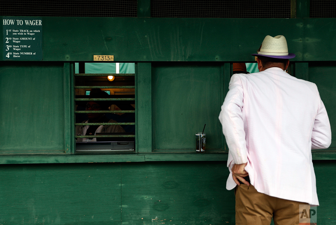 A man places a bet before the 143rd running of the Kentucky Derby horse race at Churchill Downs, Saturday, May 6, 2017, in Louisville, Ky. (AP Photo/John Minchillo)