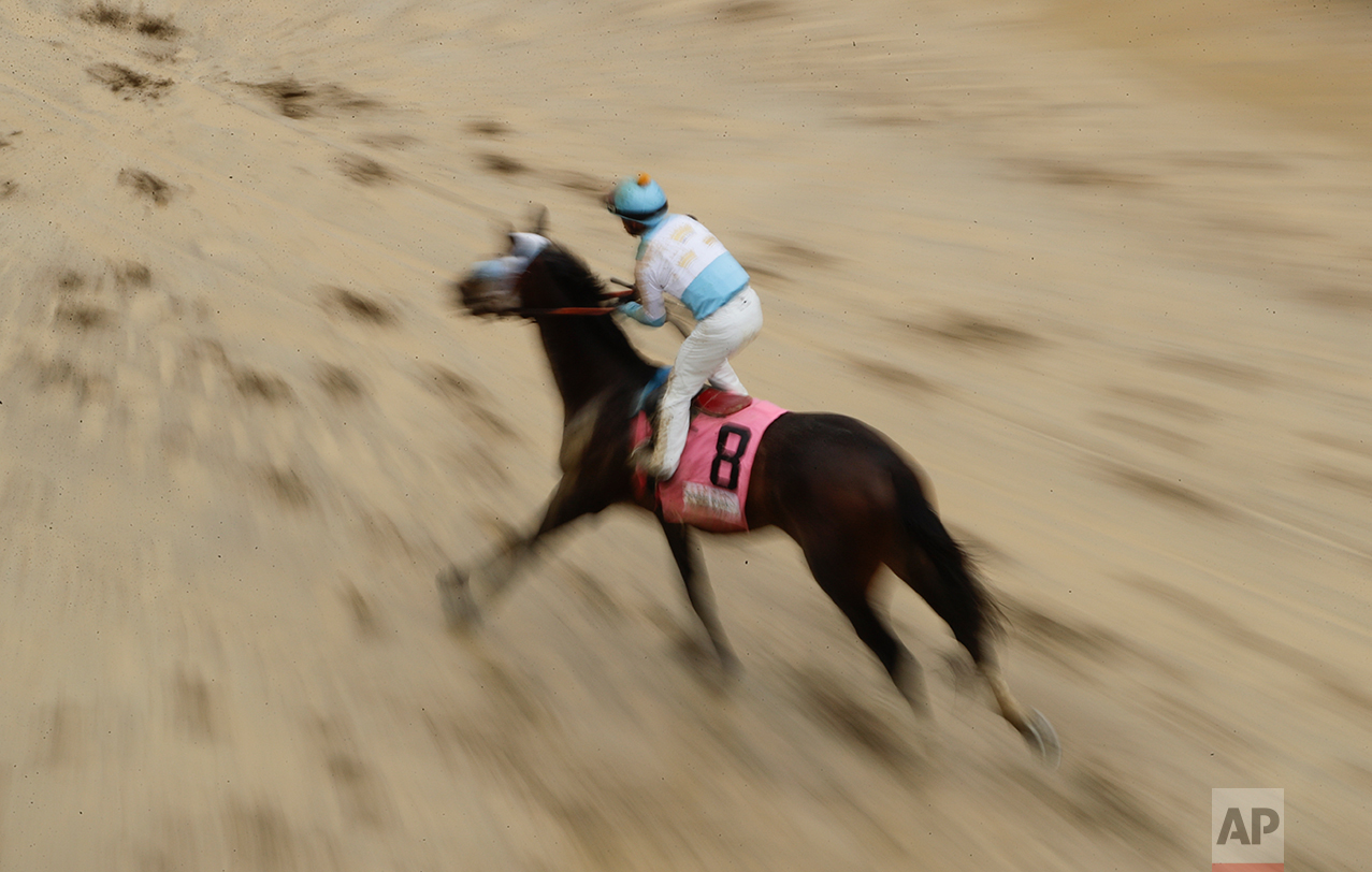 A horse runs in the mud after a race before the 143rd running of the Kentucky Derby horse race at Churchill Downs Saturday, May 6, 2017, in Louisville, Ky. (AP Photo/Charlie Riedel)