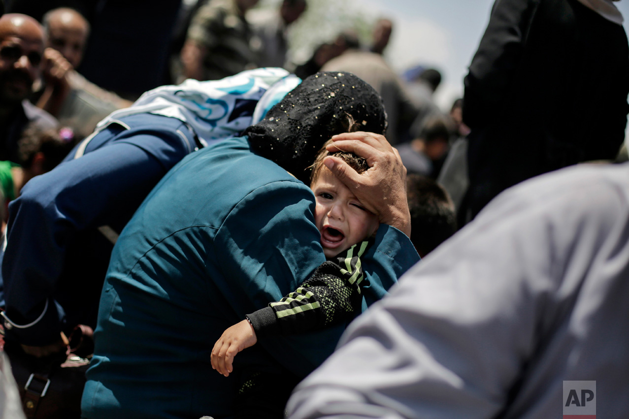 A child cries onboard a ferry to cross the Tigris River, Friday, May 5, 2017. Mosul residents are returning from the west to the liberated eastern part of the city. The government fight against Islamic State fighters for Mosul's west has been slow and deadly to Iraqi forces and civilians caught in the crossfire. (AP Photo/Bram Janssen)