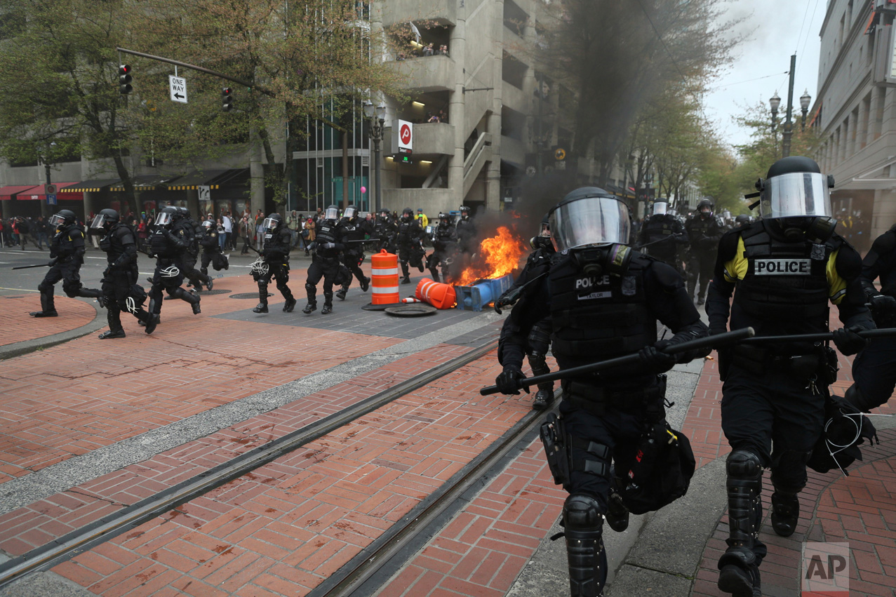 Police officers disperse people participating in a May Day rally in downtown Portland, Ore., Monday, May 1, 2017. Over 100 police officers clad in body armor and gas masks shut down a march they said had become a riot late Monday and arrested people on charges ranging from disorderly conduct to arson and assault. (Dave Killen/The Oregonian via AP)