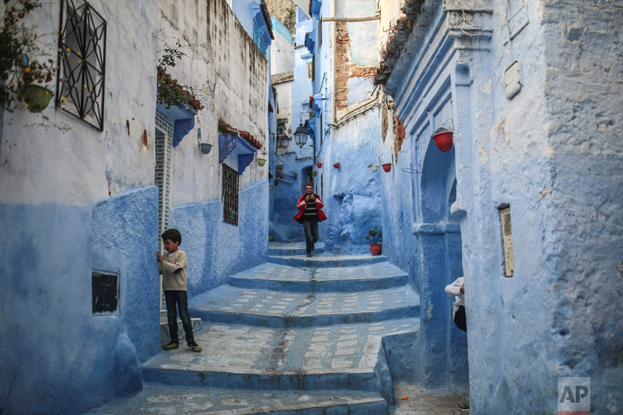 A boy plays outside his house as a man walks down the alleyway in the Medina of Chefchaouen, a town famous for its blue-painted houses and alleyways, in northern Morocco on Saturday, April 29, 2017. (AP Photo/Mosa'ab Elshamy)