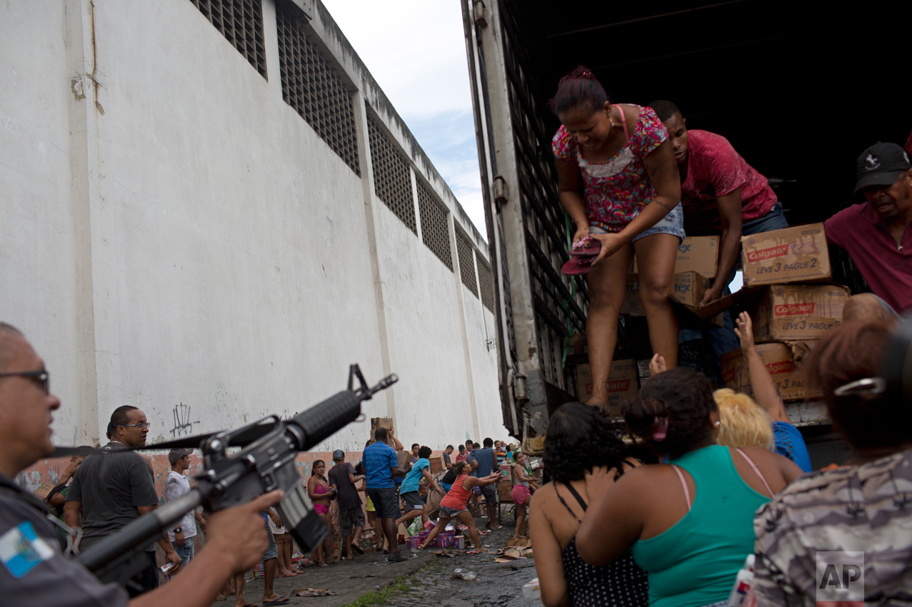 A police officer aims his weapon at people looting a truck, allegedly set on fire by drug traffickers, in Rio de Janeiro, Brazil, on Tuesday, May 2, 2017. Several public buses and cargo trucks were torched in Rio in what Brazilian military police said was likely gang retaliation for a large anti-drug operation. (AP Photo/Silvia Izquierdo)