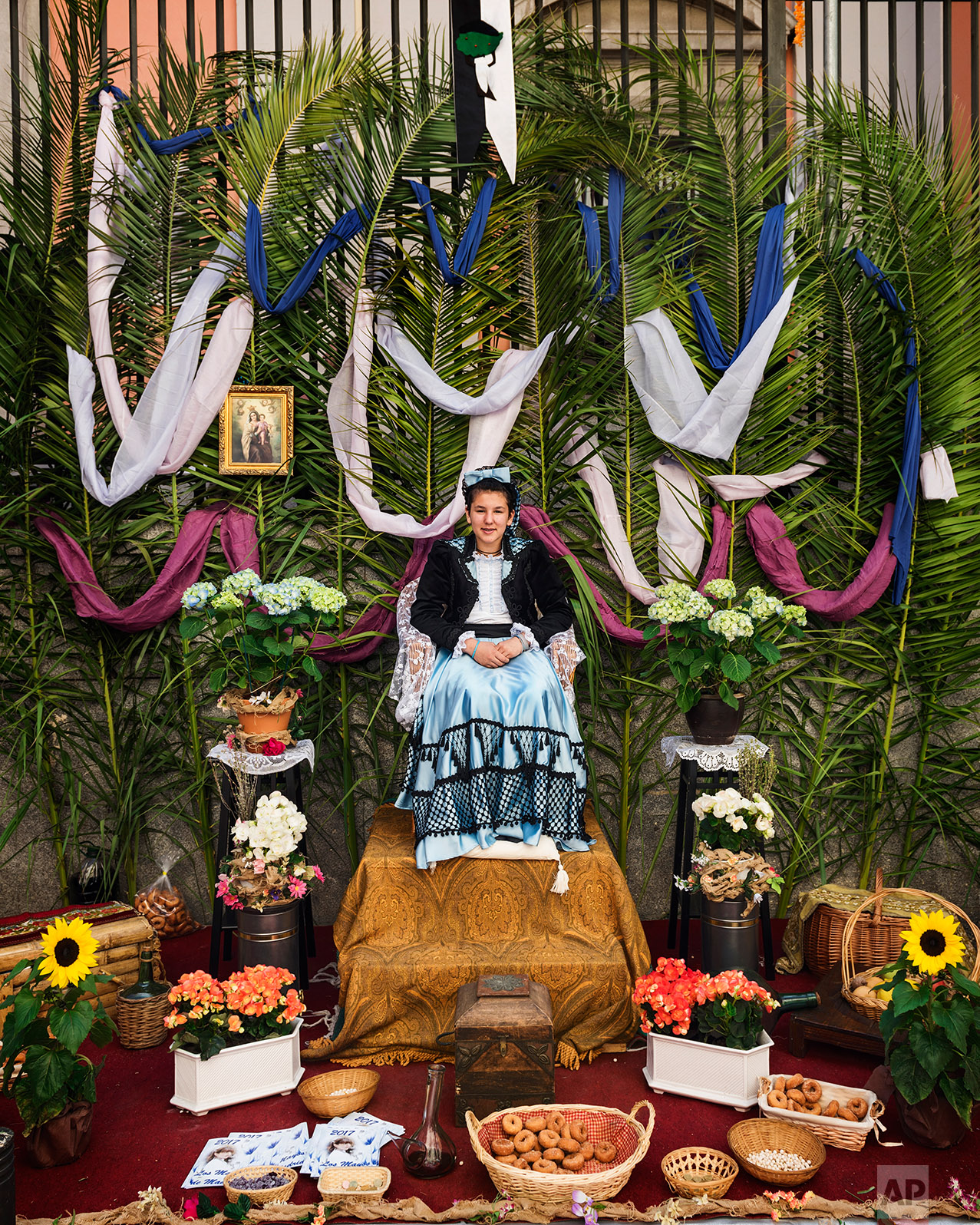 A 'Maya' girl sits in an altar during the traditional celebration of 'Las Mayas' on the streets in Madrid, Spain Sunday, May 7, 2017. (AP Photo/Daniel Ochoa de Olza)