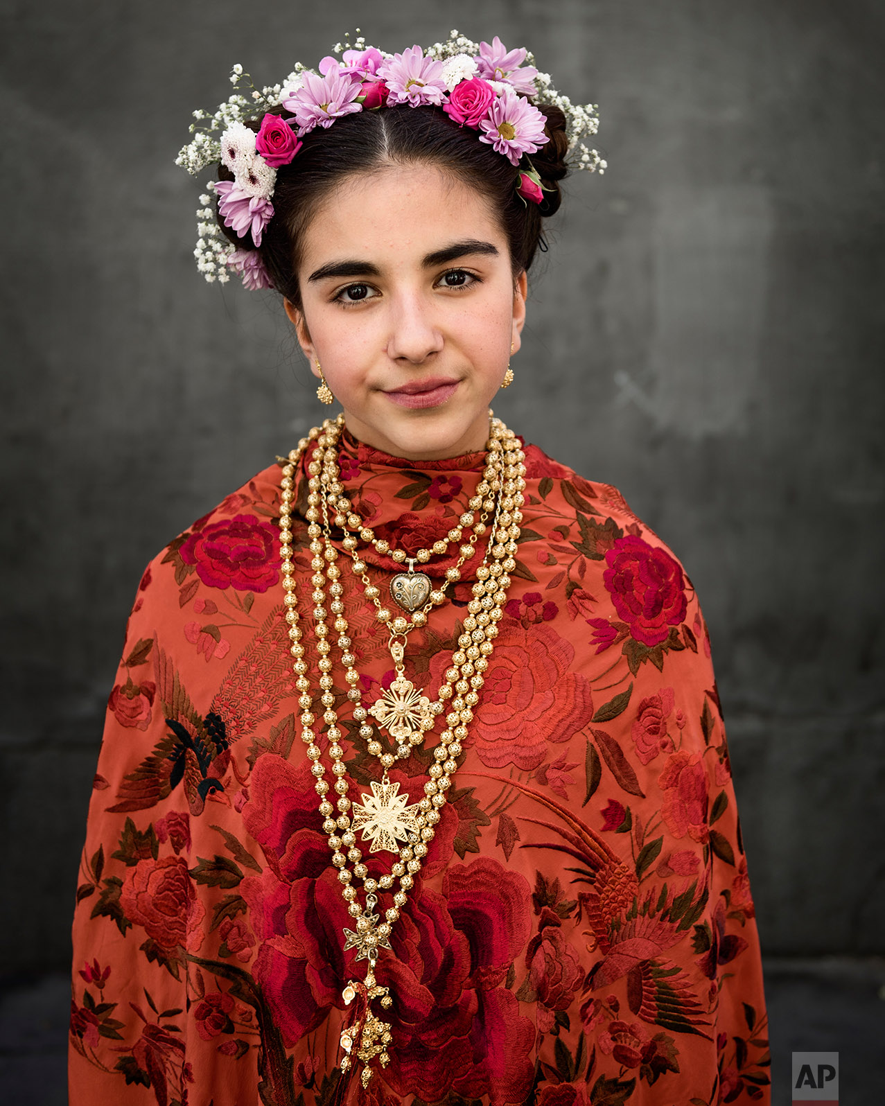 A 'Maya' girl poses for a picture after sitting in an altar during the traditional celebration of 'Las Mayas' on the streets in Madrid, Spain Sunday, May 7, 2017. (AP Photo/Daniel Ochoa de Olza)
