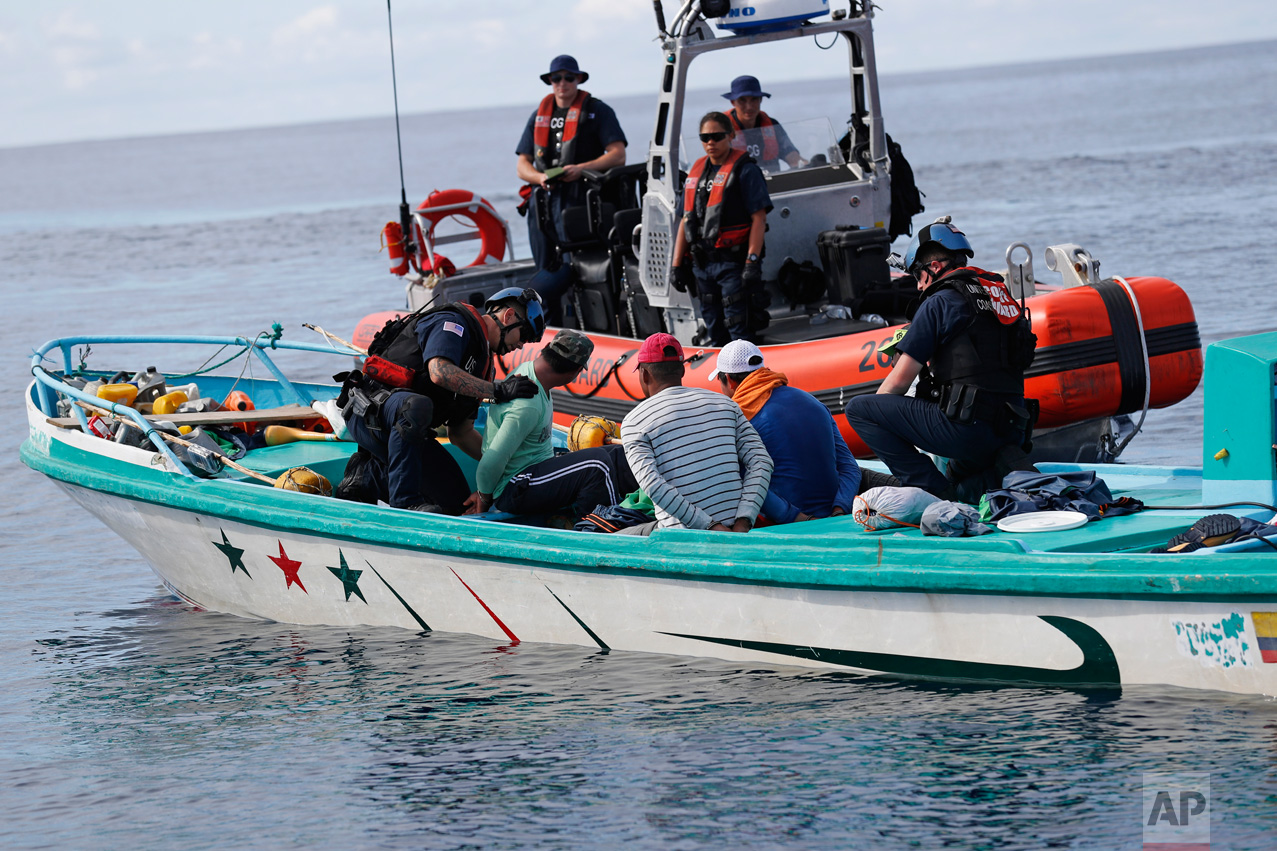 In this Feb. 23, 2017 photo, a U.S. Coast Guard law enforcement team from the USCG cutter Stratton boards a small fishing boat that was stopped for inspection in the Pacific Ocean, hundreds of miles south of the Guatemala-El Salvador border. The four suspected smugglers, two Colombians and two Ecuadoreans, were transporting approximately 700 kilos of pure cocaine. (AP Photo/Dario Lopez-Mills)