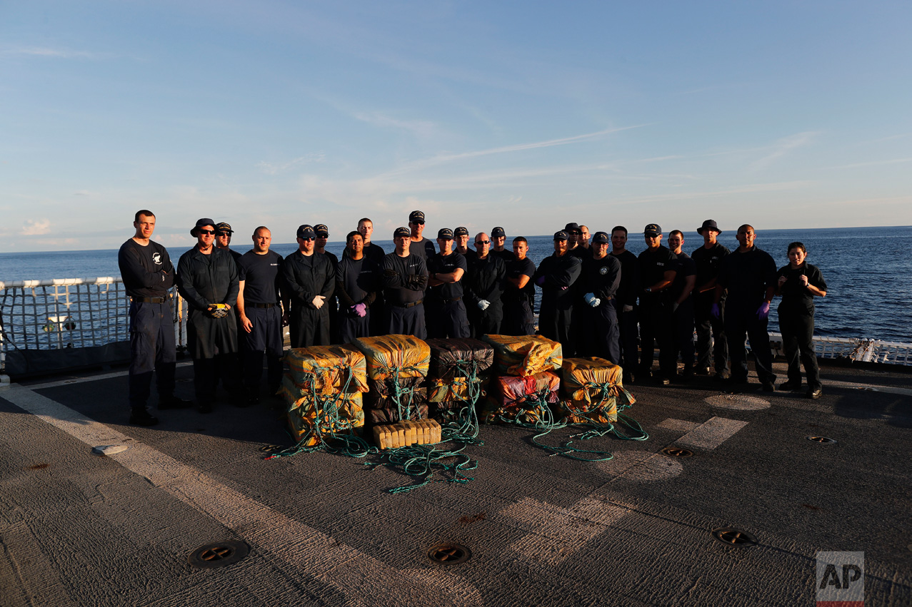 In this Feb. 23, 2017 photo, part of the crew from the U.S. Coast Guard cutter Stratton stand for a photo in front of close to 700 kilograms of pure cocaine that were seized from a small fishing boat in Pacific Ocean, hundreds of miles south of the Guatemala-El Salvador border. Four men, two from Colombia and two from Ecuador, were also detained in the operation. (AP Photo/Dario Lopez-Mills)