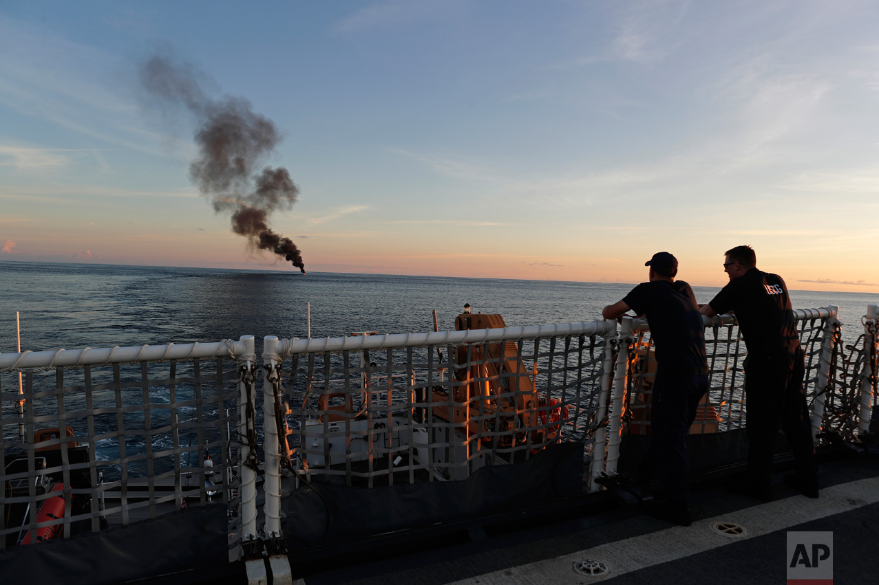 In this Feb. 23, 2017 photo, two Coast Guardsmen watch from the U.S. Coast Guard cutter Stratton as a small fishing boat was set ablaze by the Coast Guard after close to 700 kilograms of cocaine were seized and four men were detained, in the Pacific Ocean, hundreds of miles south of the Guatemala-El Salvador border. A few hours later, the Stratton fired its cannon and sank the boat. (AP Photo/Dario Lopez-Mills)