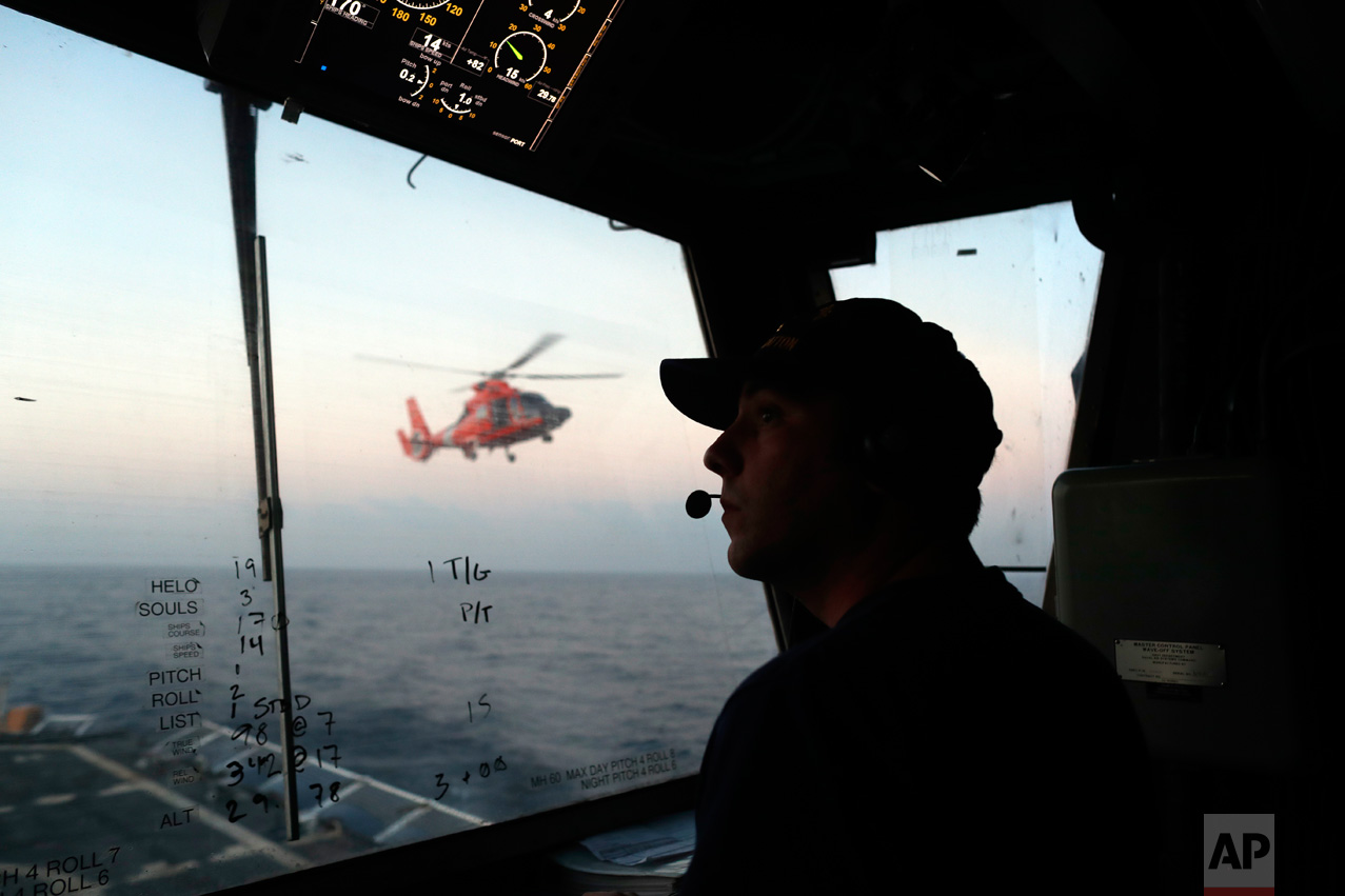 In this March 2, 2017 photo, an unidentified U.S. Coast Guardsman communicates with the pilot of a helicopter during take-off and landing exercises on the U.S. Coast Guard cutter Stratton in the eastern Pacific Ocean. For its drug interdiction operations, the Coast Guard is bringing more intelligence and technology to bear. Deep within the Stratton, specialists crunch data from radar, infrared video, helicopter sorties as well as other available sources. (AP Photo/Dario Lopez-Mills)