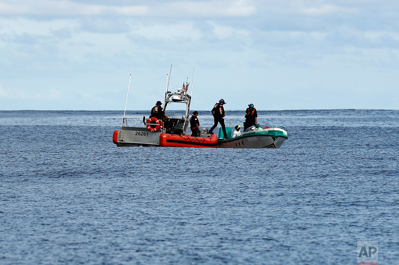 In this Feb. 23, 2017 photo, a U.S. Coast Guard law enforcement team from the USCG cutter Stratton boards a small fishing boat that was stopped carrying close to 700 kilos of pure cocaine, in the Pacific Ocean hundreds of miles south of the Guatemala-El Salvador border. Sometimes smugglers frantically dump their cargo over the side or try to make a run for it, forcing their pursuers to fire warning shots or shoot out their engines. But this time the crew members, some of them barefoot, offered no resistance. (AP Photo/Dario Lopez-Mills)