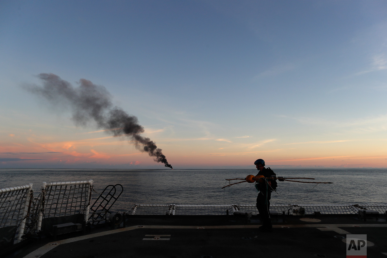 In this Feb. 23, 2017 photo, a Coast Guardsmen walks on the flight deck of the U.S. Coast Guard cutter Stratton carrying items found in a small fishing boat that was set ablaze by the Coast Guard after close to 700 kilograms of cocaine were seized in the Pacific Ocean, hundreds of miles south of the Guatemala-El Salvador border. One of the Coast Guard's main missions is to intercept vessels hauling cocaine bound for America's cities. It is a monumental task that has grown even larger in the past few years because of a boom in coca production in Colombia. (AP Photo/Dario Lopez-Mills)