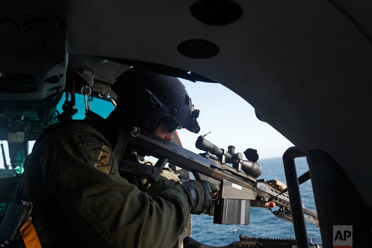 In this March 7, 2017 photo, a sharpshooter who only wished to identify himself as Matt from the USCG HITRON (United States Coast Guard Helicopter Interdiction Tactical Squadron) assigned to the U.S. Coast Guard cutter Stratton, performs a gun exercise while flying over the eastern Pacific Ocean. The Coast Guard has been coming back with ever-larger drug hauls. It set a record in 2016, seizing more than 240 tons of cocaine with a wholesale value of $5.9 billion and arresting 585 smugglers. (AP Photo/Dario Lopez-Mills)