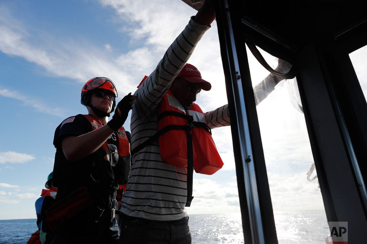 In this Feb. 23, 2017 photo, a U.S. Coast Guard law enforcement team member from the USCG cutter Stratton frisks one of the four men who were caught on a small fishing boat carrying close to 700 kilos of pure cocaine, in the Pacific Ocean hundreds of miles south of the Guatemala-El Salvador border. Sometimes smugglers frantically dump their cargo over the side or try to make a run for it, forcing their pursuers to fire warning shots or shoot out their engines. But this time the crew offered no resistance. (AP Photo/Dario Lopez-Mills)