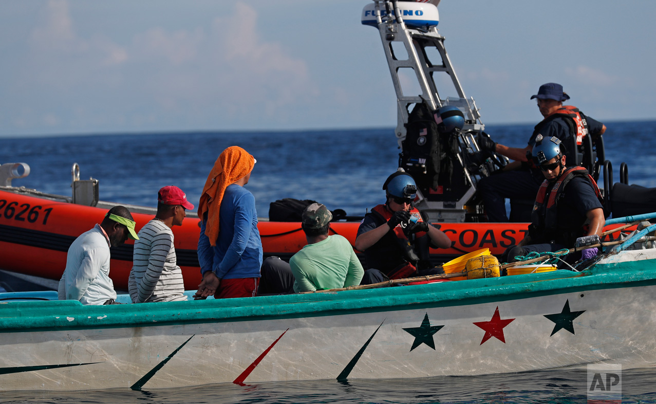 In this Feb. 23, 2017 photo, a U.S. Coast Guard law enforcement team from the USCG cutter Stratton boards a small fishing boat that was stopped for inspection in the Pacific Ocean, hundreds of miles south of the Guatemala-El Salvador border. The four suspected smugglers aboard sat handcuffed as a Coast Guardsman conducted a chemical test on the drugs. (AP Photo/Dario Lopez-Mills)