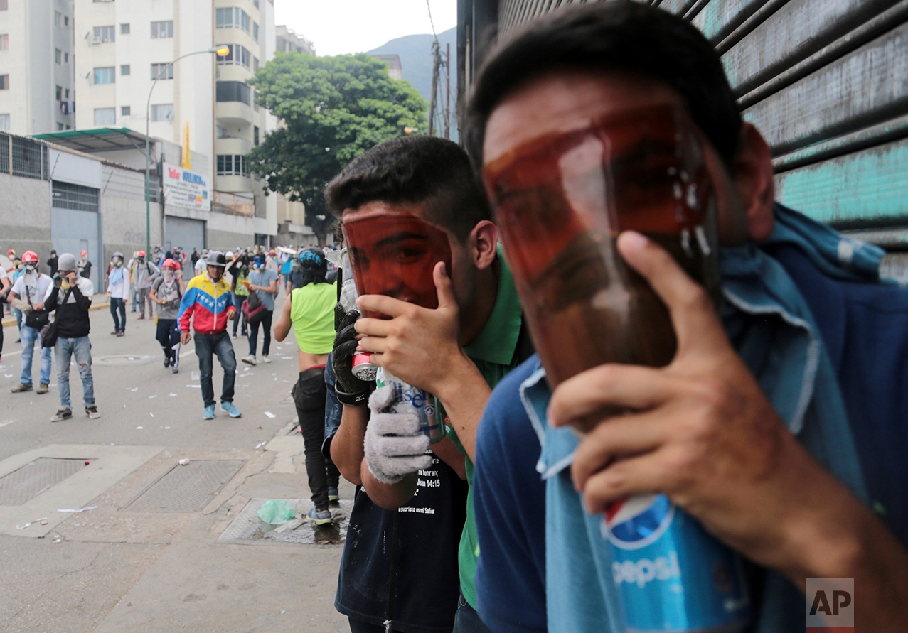 In this May 3, 2017 photo, demonstrators covers their faces with homemade tear gas masks made from plastic bottles, during a protest in Caracas, Venezuela. The opposition is vowing to remain on the streets even as the death toll mounts after six weeks of unrest, arming themselves with makeshift armor and weapons for what could be a protracted conflict. (AP Photo/Fernando Llano)