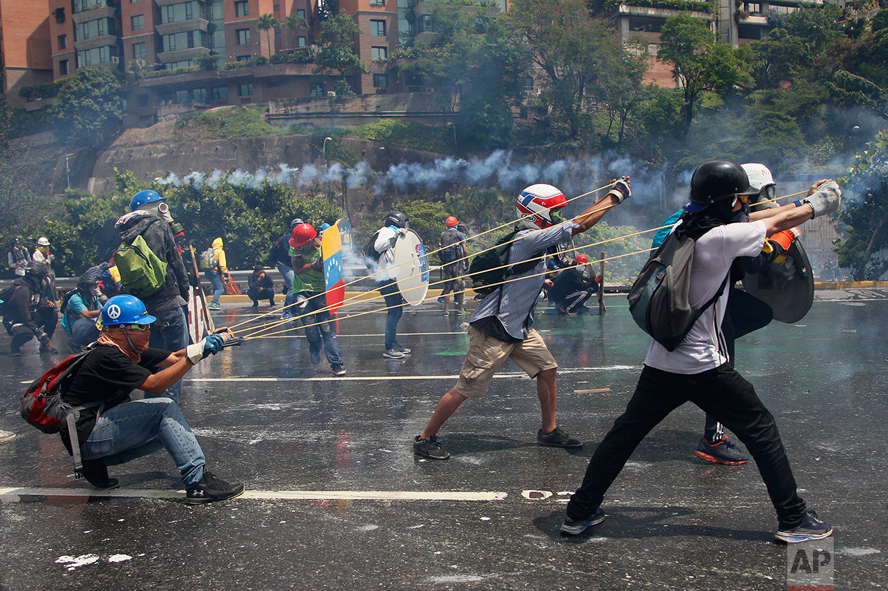 "In this May 10, 2017 photo, anti-government protesters work together to aim a giant slingshot holding a glass bottle filled with feces, at security forces blocking their march from reaching the Supreme Court in Caracas, Venezuela. Protesters write messages like ""For the political prisoners!"" and ""Sent with love"" on the containers. (AP Photo/Ariana Cubillos)"