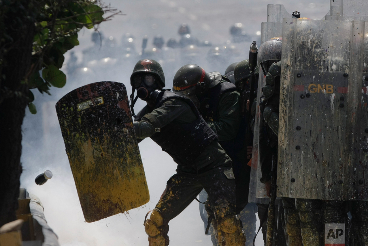 In this May 10, 2017 photo, Bolivarian National Guards shield themselves from a jar filled with fecal matter, thrown by anti-government protesters in Caracas, Venezuela. The government has denounced use of the feces-filled bombs, equating them to a type of biochemical weapon that could spread illnesses. (AP Photo/Fernando Llano)