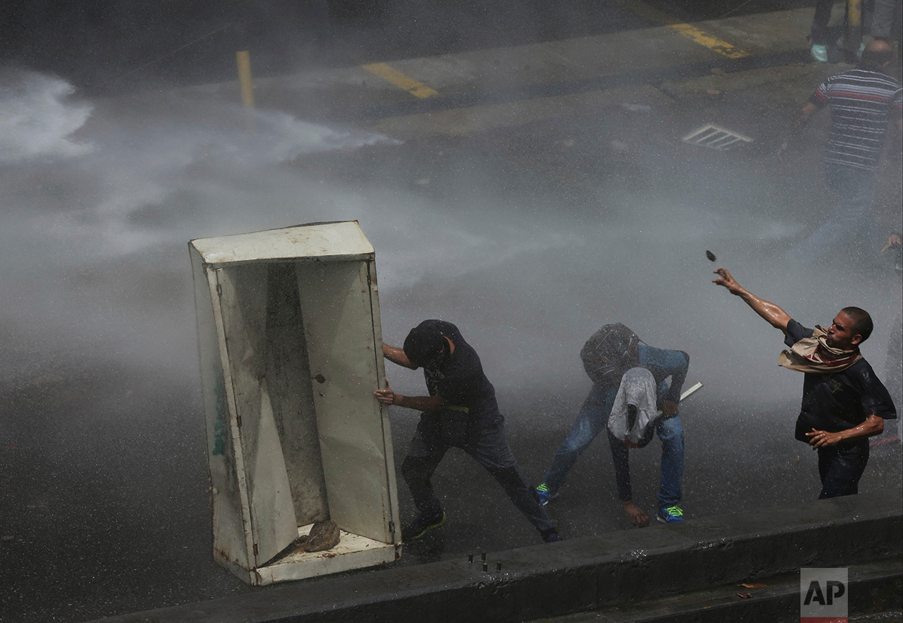"In this April 6, 2017 photo, demonstrators use a metal cabinet as a shield as they take cover from a police water cannon during an anti-government protest in Caracas, Venezuela. ""We are using these devices to protect ourselves, to prevent there from being more injuries than there have already been,"" Juan Andres Mejia, an opposition lawmaker, said this week as a friend held a wooden shield above his head. (AP Photo/Fernando Llano)"