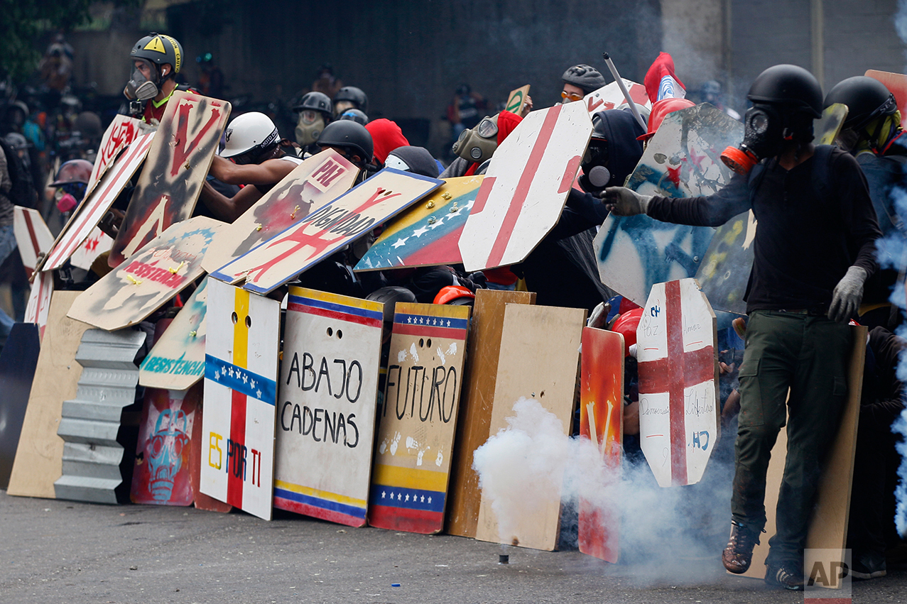 In this May 8, 2017 photo, anti-government protesters use handmade shields as they face off with security forces blocking a student march from reaching the Education Ministry in Caracas, Venezuela. Hundreds of thousands have taken to the streets to castigate President Nicolas Maduro's administration, which they claim has become a dictatorship responsible for triple-digit inflation, skyrocketing crime and crippling food shortages. (AP Photo/Ariana Cubillos)