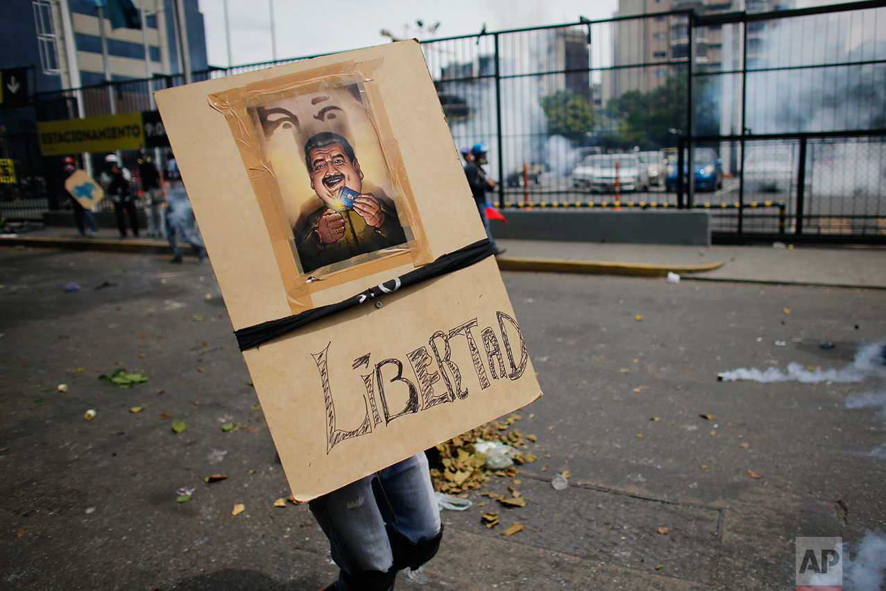 "In this May 8, 2017 photo, an anti-government demonstrator carries a homemade shield depicting Venezuela's President Nicolas Maduro burning the country's constitution, and with a message that reads in Spanish: ""Freedom"" in Caracas, Venezuela. Protesters mass behind wooden shields bearing medieval decorations or images of the South American nation's blue constitution book, which Maduro wants to rewrite. (AP Photo/Ariana Cubillos)"