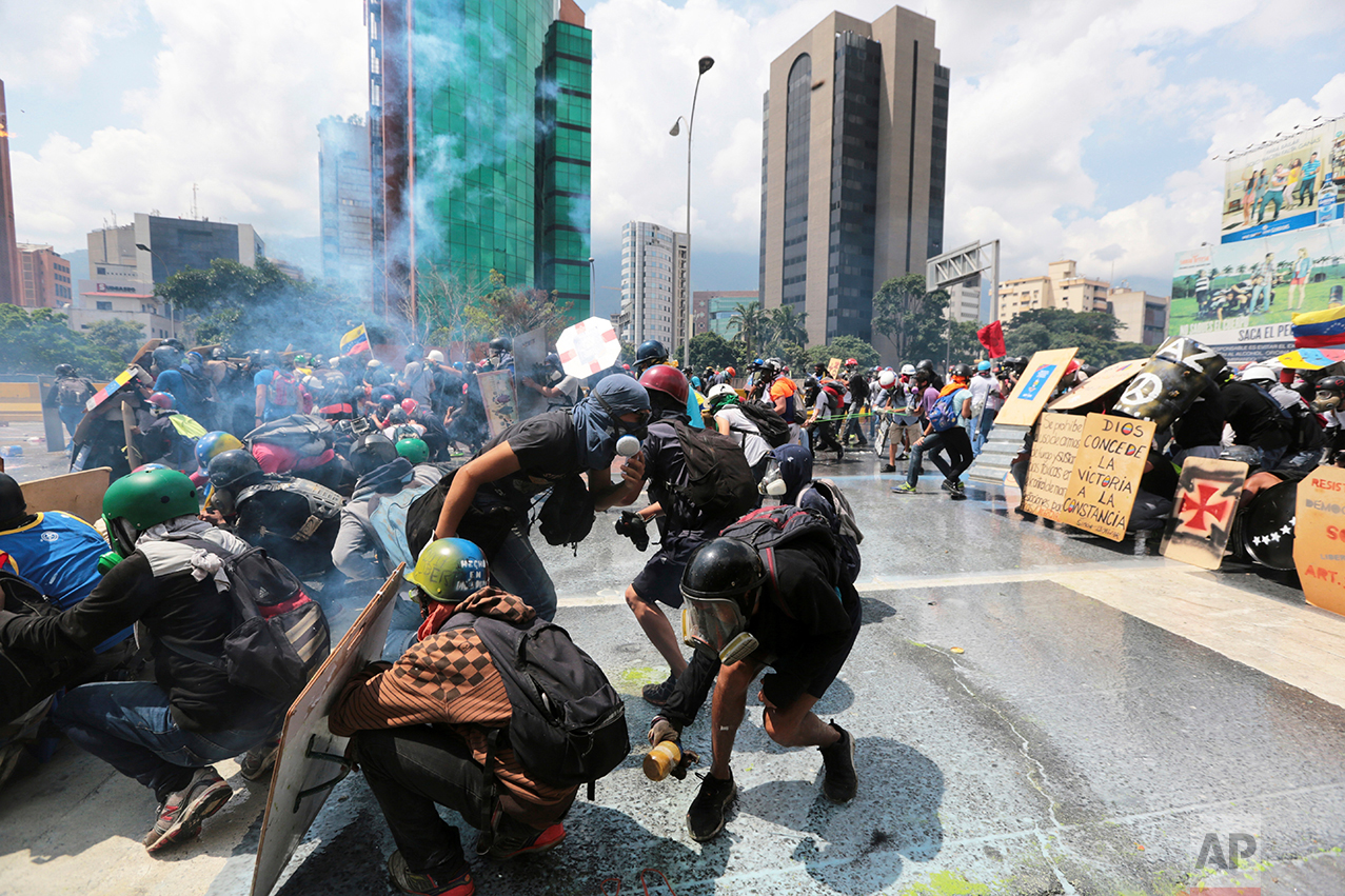 "In this May 10, 2017 photo, a demonstrator, right center, holds a glass bottle filled with feces, known as a ""puputov,""  to throw at Bolivarian National Guards during clashes with security forces at an anti-government protest in Caracas, Venezuela. In front of the protesters stands a line of officers equipped with bulletproof vests, visored helmets and plastic shields to protect themselves from the rocks and ""puputovs"" that some demonstrators throw their way. (AP Photo/Fernando Llano)"