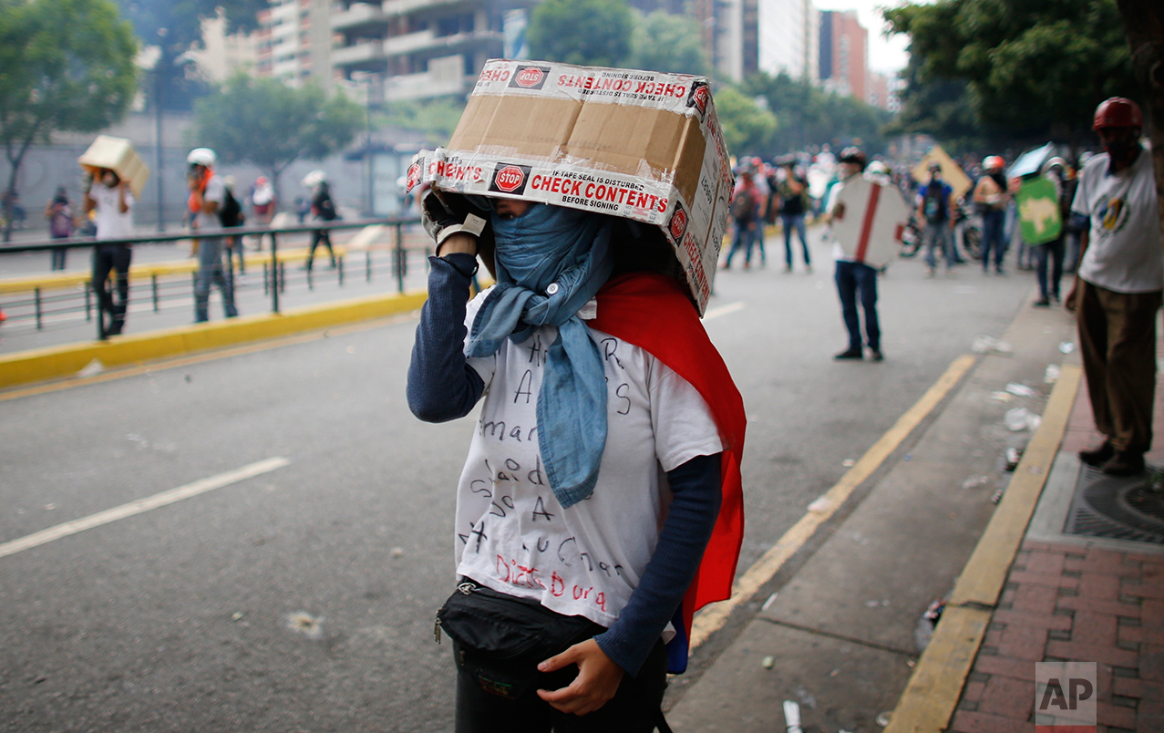 In this May 8, 2017 photo, a woman protects her head with a box during an anti-government protest in Caracas, Venezuela. Some protesters wear swimming goggles to protest their eyes from the stinging gas. Others use gas masks fashioned from soda bottles. (AP Photo/Ariana Cubillos)
