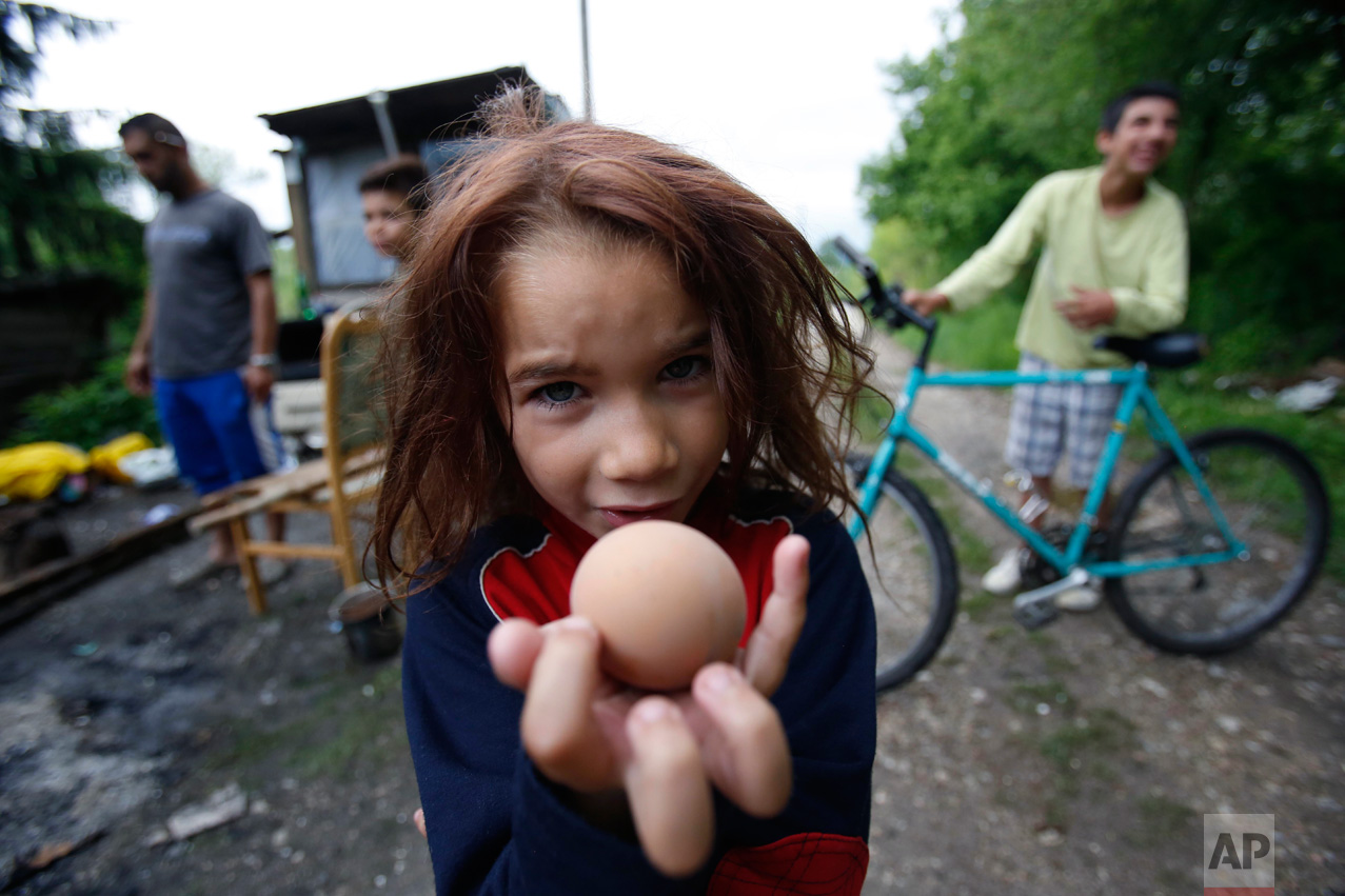 Roma girl Samira Ramic holds a boiled egg as she poses for a photo during a St. George's Day celebration with her family, in the village of Kiseljak, near Tuzla, Bosnia-Herzegovina, 140 kilometers (87 miles) north of Sarajevo, on Saturday, May 6, 2017. Members of the Roma minority community in the country celebrated their biggest holiday, St. George's Day (Djurdjevdan), marking the advent of spring, with traditional rituals such as using water from church wells to bathe and their wash hands, and cracking eggs. (AP Photo/Amel Emric)