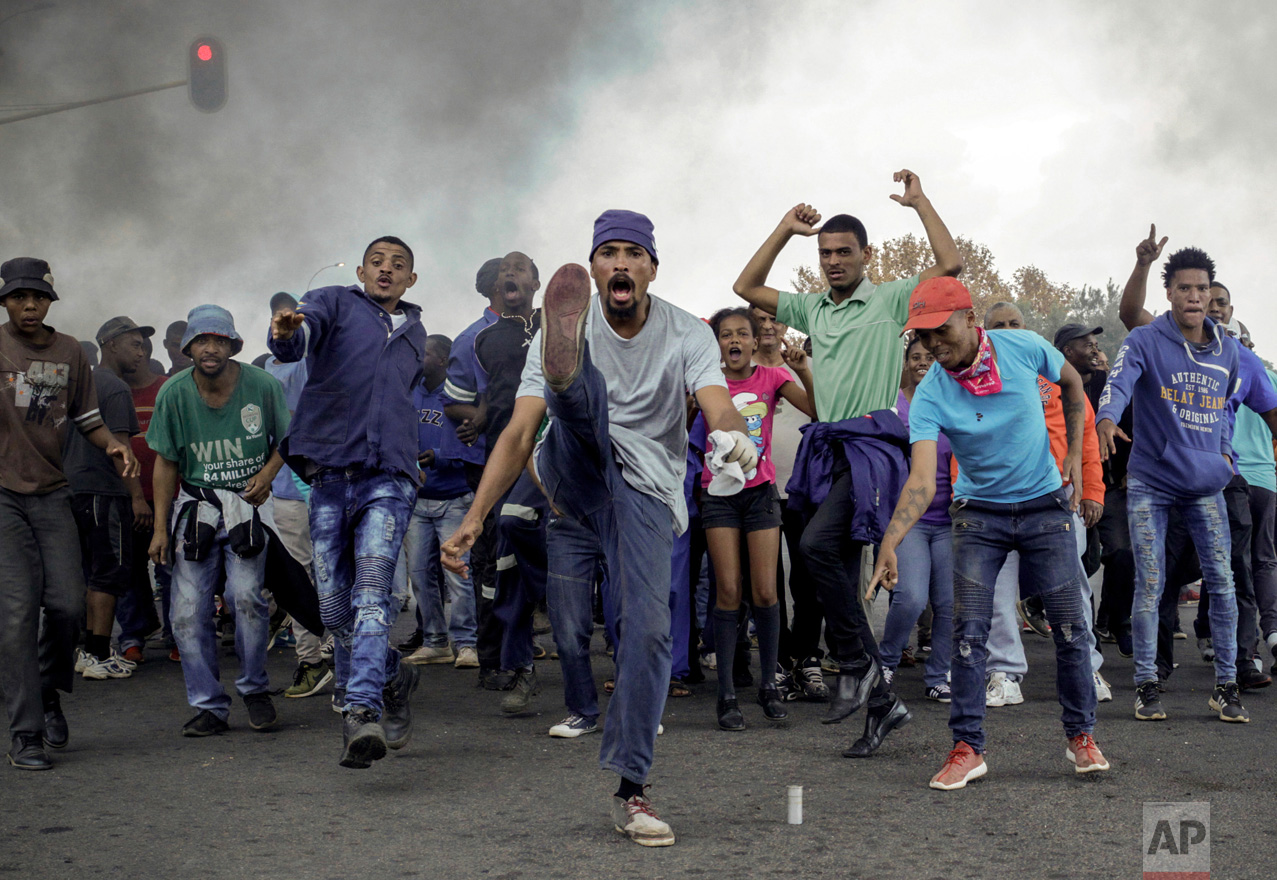 Protesters sing and chant in front of a burning barricade in the Ennerdale, Johannesburg township of South Africa on Tuesday, May 9, 2017. Violent protests have erupted in South Africa's biggest city for a second day as protesters demand housing and other government services. (AP Photo)