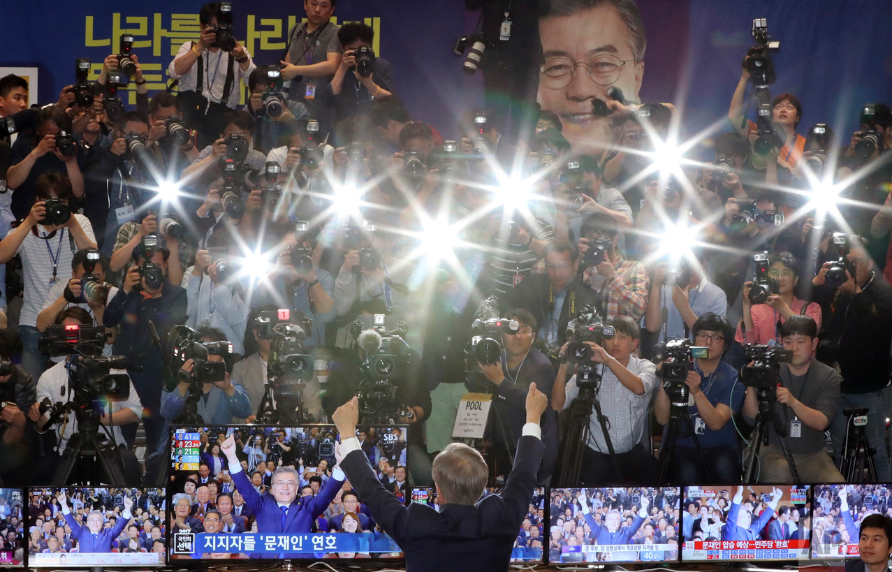 Presidential candidate Moon Jae-in of the Democratic Party raises his arms for photographers as his party leaders, members and supporters watch results of exit polls for the presidential election at National Assembly in Seoul, South Korea, Tuesday, May 9, 2017. South Korea's new president is taking on a challenge that has defied all of his predecessors: reforming the big family-controlled conglomerates that dominate the economy. (AP Photo/Lee Jin-man)