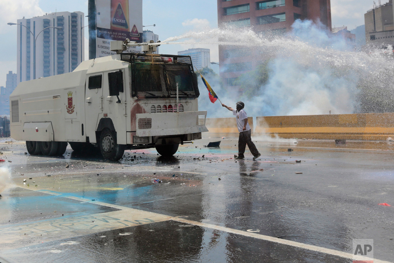 An anti-government protester points a Venezuelan flag at a security forces in a water canon vehicle during an opposition march in Caracas, Venezuela, on Wednesday, May 10, 2017. Opponents of President Nicolas Maduro attempted to march to the Supreme Court to protest its decision to gut the opposition-controlled congress of its powers _ a ruling that was quickly rescinded under a barrage of international criticism but that set off weeks of political unrest that have left some three dozens killed. (AP Photo/Fernando Llano)