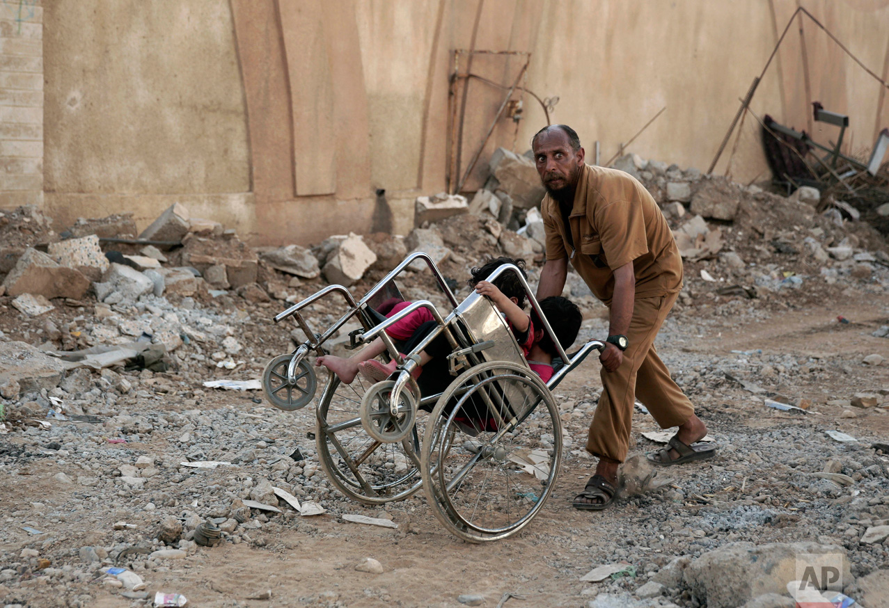 A man pushes two children in a wheelchair as they flee heavy fighting between Islamic State militants and Iraqi special forces in Mosul, Iraq, Wednesday, May 10, 2017. Iraqi army, federal police and special forces, backed by the U.S.-led coalition, are slowly retaking territory in Mosul where IS remains in control of a small cluster of neighborhoods in the city's western half. (AP Photo/Maya Alleruzzo)