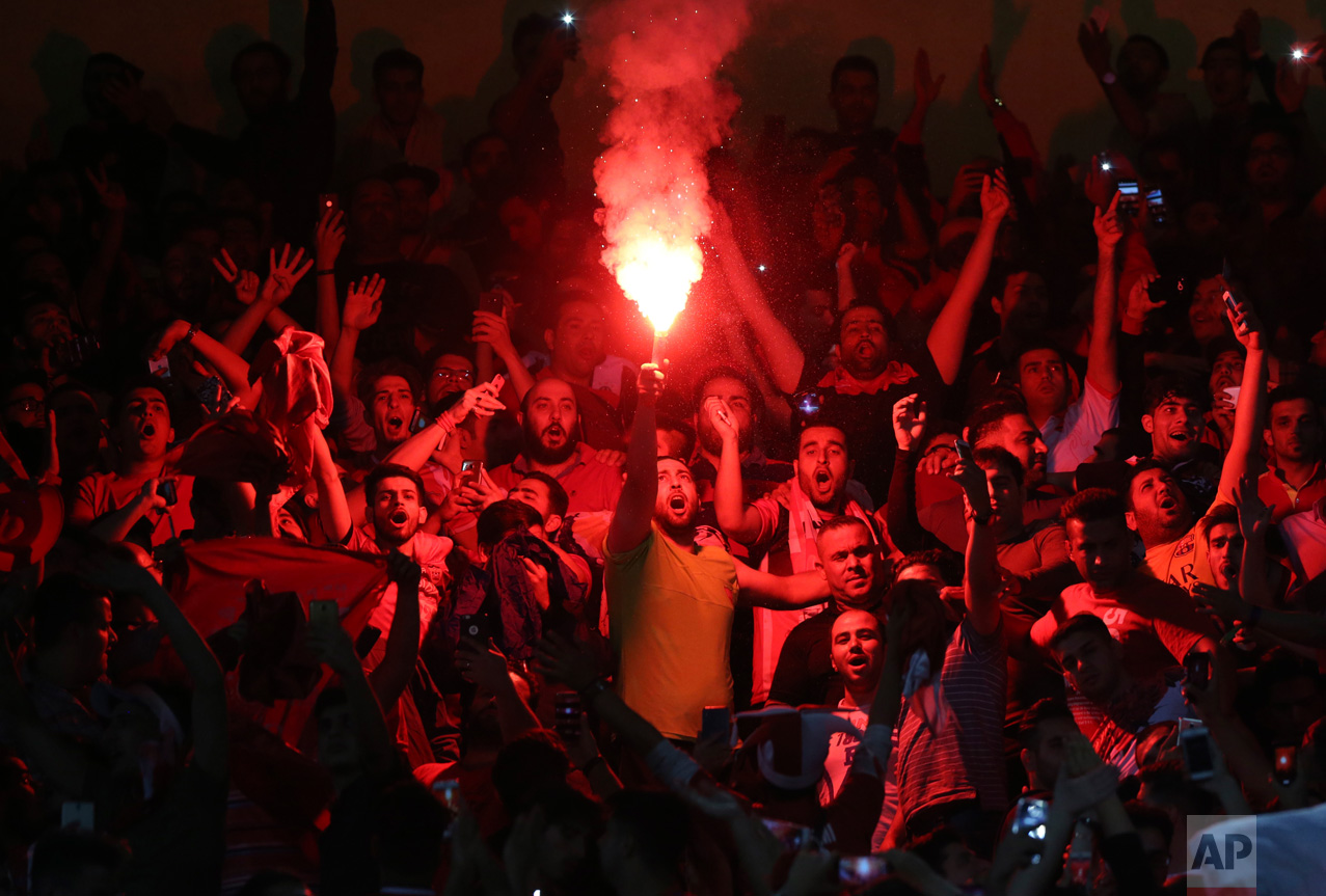 A fan of Persepolis ignites a flare during an AFC Champions League soccer match against Al Wahda at the Azadi stadium in Tehran, Iran, Monday, May, 8, 2017. Persepolis won the match 4-2. (AP Photo/Vahid Salemi)