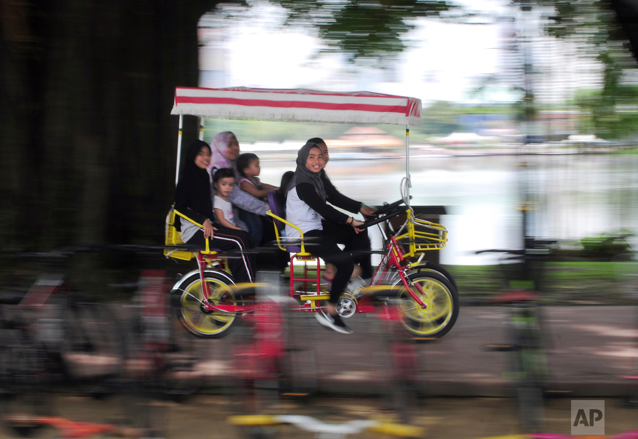A family rides a cycle together at the Titiwangsa lake gardens in Kuala Lumpur, Malaysia, on Saturday, May 6, 2017. Titiwangsa lake gardens is a recreational park with a large lake located in the north-eastern fringe of Kuala Lumpur city center. (AP Photo/Daniel Chan)