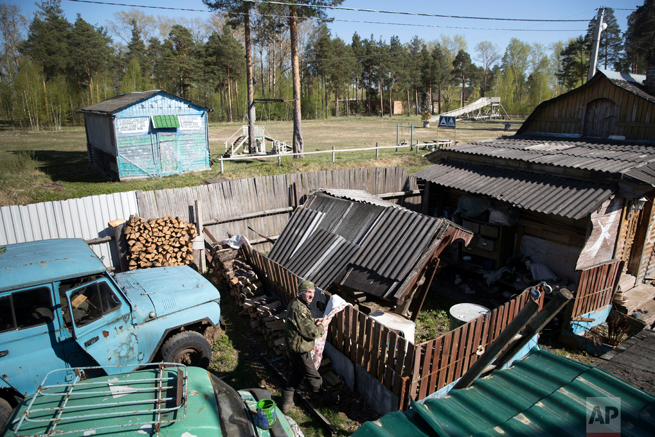 In this photo taken on Wednesday, May 3, 2017, Mikhail Korhunov stands in a yard of his house in the village of Severnaya Griva, about 130 kilometers (80 miles) east of Moscow, Russia. In this sparsely populated village east of Moscow, Mikhail Korshunov's house is visible from far away. Portraits of Russian rulers - from 13th century Novgorod prince Alexander Nevsky to President Vladimir Putin - adorn its facade. (AP Photo/Pavel Golovkin)