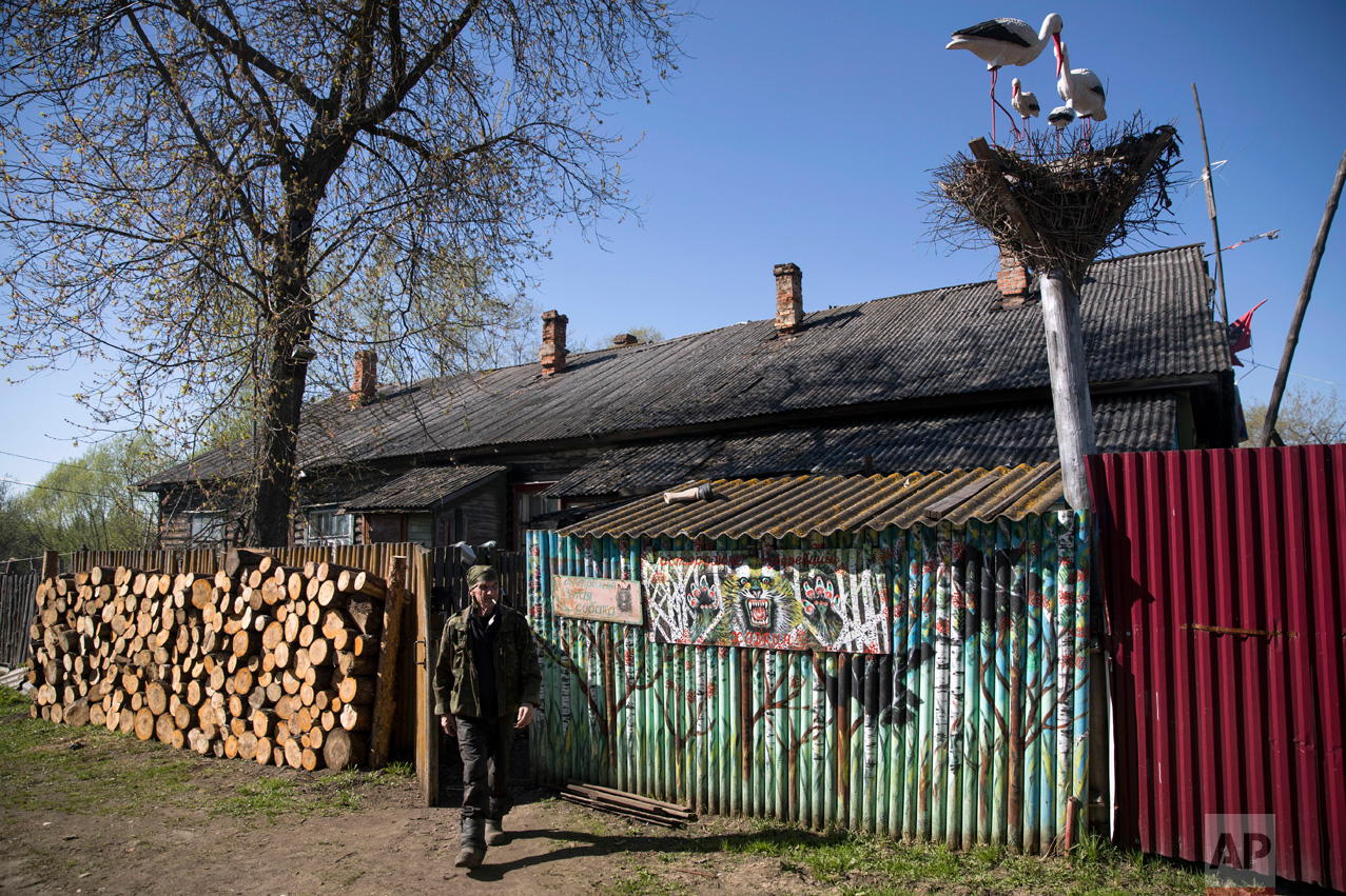 In this photo taken on Wednesday, May 3, 2017, Mikhail Korhunov walks in a yard of his house in the village of Severnaya Griva, about 130 kilometers (80 miles) east of Moscow, Russia. (AP Photo/Pavel Golovkin)