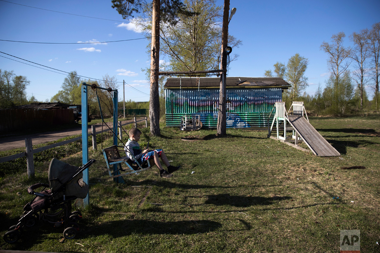 In this photo taken on Wednesday, May 3, 2017, a boy plays on a swing in the village of Severnaya Griva, about 130 kilometers (80 miles) east of Moscow, Russia. The swings and a wooden slope were built by Mikhail Korhunov. (AP Photo/Pavel Golovkin)
