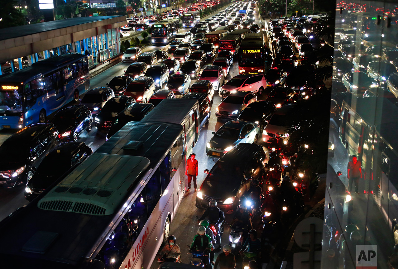 A city bus crew member stands next to his vehicle as he is illuminated red by the tail lights of other vehicles in rush hour traffic in Jakarta, Indonesia, Friday, May 19, 2017. (AP Photo/Dita Alangkara)